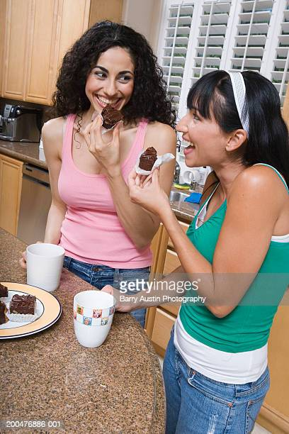 Two women eating cakes in kitchen, smiling