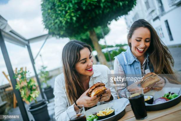 Two women eating Hamburgers in a street restaurant