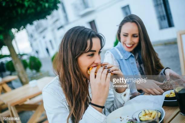 Two women eating Hamburgers in a street restaurant