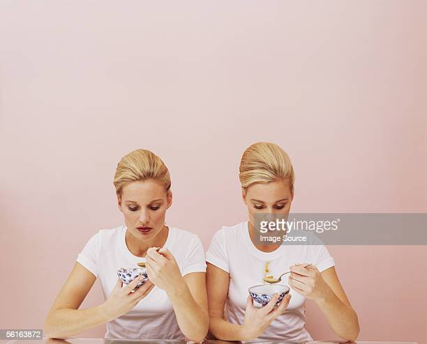 two women eating soup - twin stock pictures, royalty-free photos & images