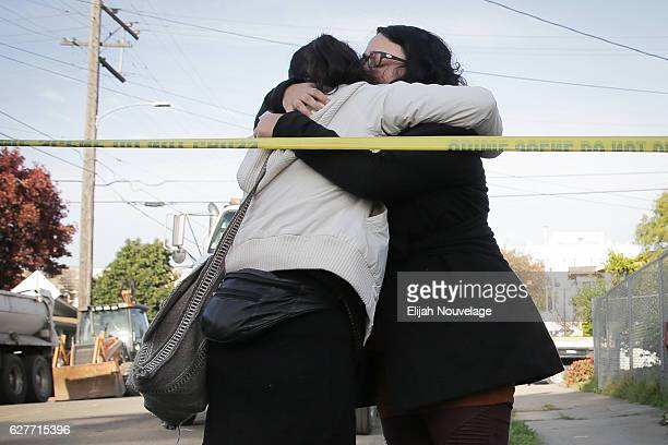 Two women embrace following a small ceremony near the site of a warehouse fire that has claimed the lives of at least thirtythree people on December...