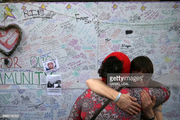 TOPSHOT Two women embrace in front of a messages left on a wall of condolence following the blaze at Grenfell Tower a residential tower block in west...