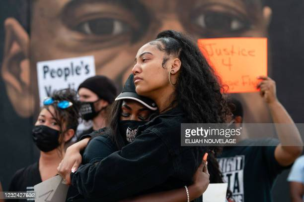 Two women embrace in front of a mural of George Floyd following the guilty verdict the trial of Derek Chauvin on April 20 in Atlanta, Georgia. -...