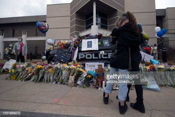 Two women embrace outside of the Boulder Police Department in Boulder, Colorado, on March 25, 2021 to pay their respects to Boulder Police officer...