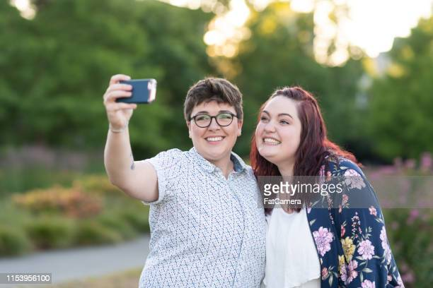 two women embracing and taking a selfie on an evening walk - downtown comedy duo stock pictures, royalty-free photos & images