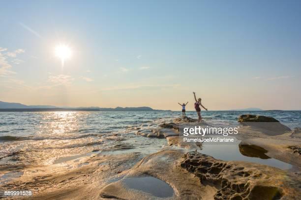 Dos mujeres abrazándose naturaleza con Outsretched armas en la remota Playa