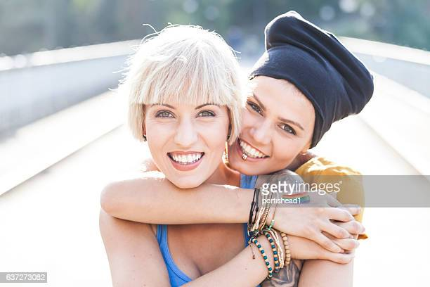 Two women embracing on bridge and looking at camera