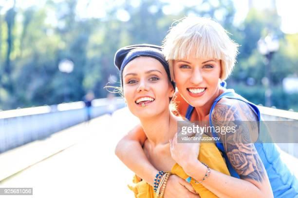 deux femmes embrassant sur pont et regardant la caméra - intersex photos et images de collection