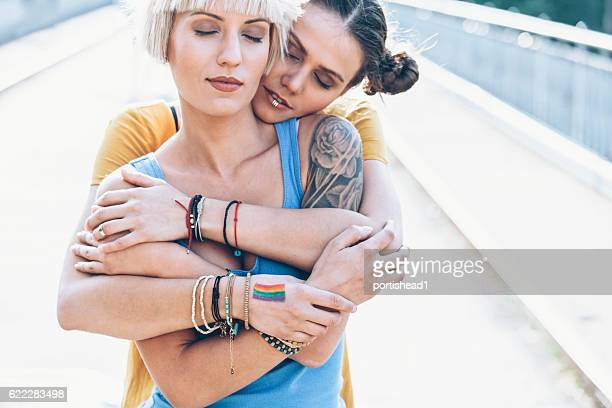 Two women embracing on bridge with eyes closed