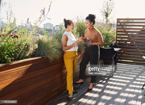 two women enjoying a drink together after work - sally anscombe stock pictures, royalty-free photos & images