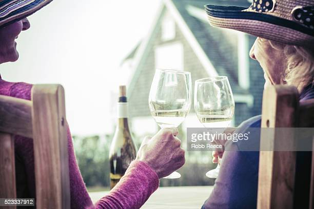 two women enjoying a glass of wine outdoors in nantucket, ma - robb reece bildbanksfoton och bilder