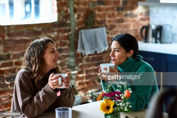 two women enjoying hot drink having conversation - discussion stock pictures, royalty-free photos & images