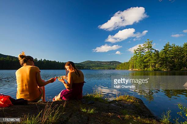 two women enjoying wine on lakeshore while camping - lake george new york stock pictures, royalty-free photos & images