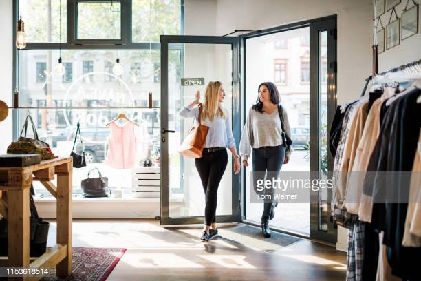 two women entering clothing store together - entrare foto e immagini stock