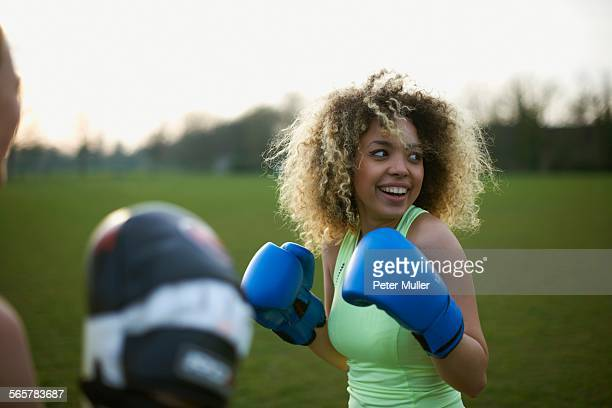 two women exercising with boxing gloves in the park - padding stock pictures, royalty-free photos & images