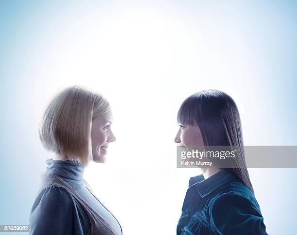 Two women facing each other and smiling
