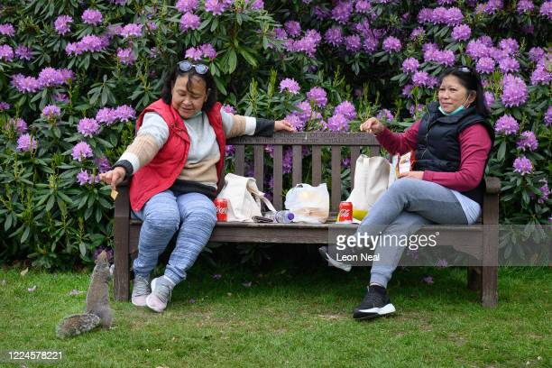 Two women feed the squirrels as they chat and enjoy a picnic on a bench in Golders Hill Park, after aspects of the lockdown were eased, on May 13,...