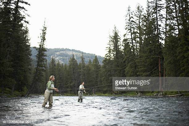Two women fly-fishing in river, side view