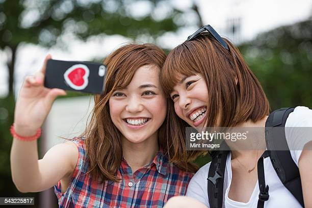 Two women, friends, taking a selfie in the park.
