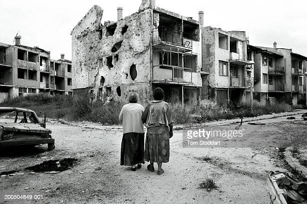 Bosnia Sarajevo April 1996Two women friends walk past destroyed houses in their devastated neighbourhood which had been heavily bombarded during the...