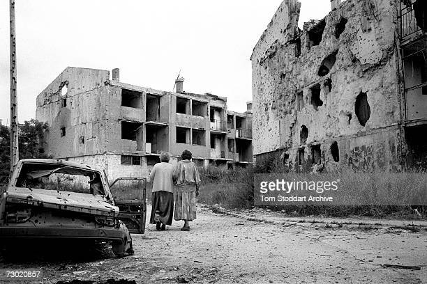 Two women friends walk past destroyed houses in their devastated neighbourhood which had been heavily bombarded during the war During the 47 months...