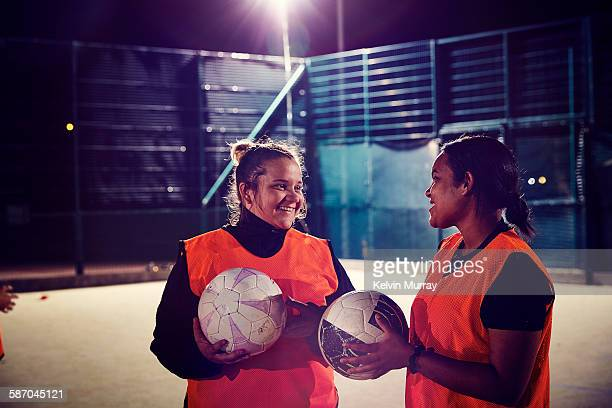 two women from ladies football team smiling - football pitch stock pictures, royalty-free photos & images