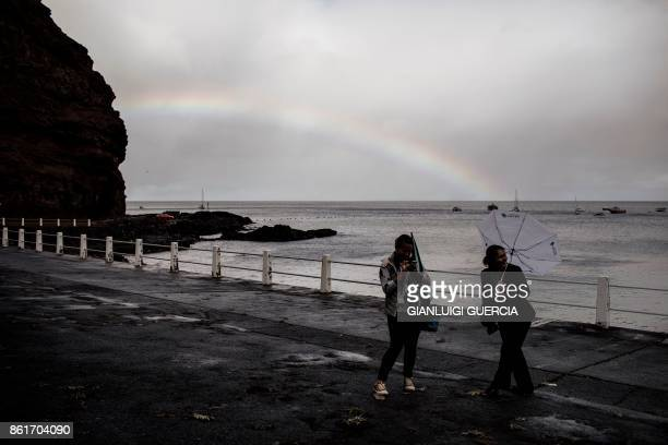 TOPSHOT Two women from Saint Helena island gesture on the seaside promenade of Jamestown the capitol of the tropical island of Saint Helena in the...
