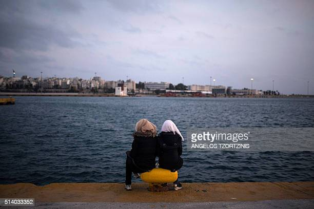 TOPSHOT Two women from Syria sit facing the sea at Piraeus harbour in Athens on March 6 2016 At least 25 migrants including children died on March 6...