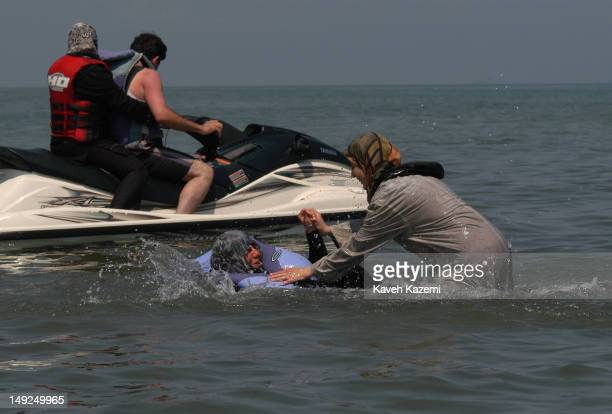 Two women fully dressed, one in traditional chador and wearing a lifejacket, enjoy a moment playing in the water under harsh summer heat exceeding 40...