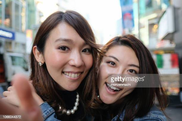 two women gathering faces and taking selfie on the street of shibuya - self portrait photography stock pictures, royalty-free photos & images