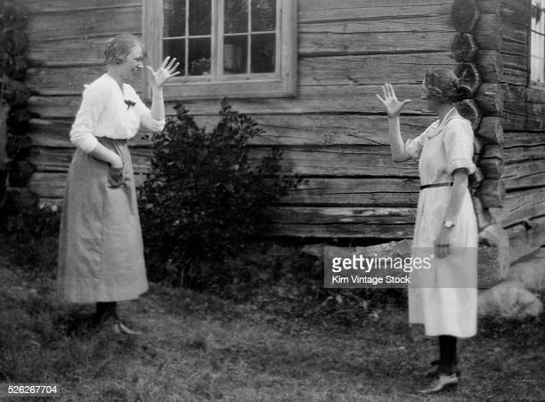 Two women gesture unkindly at each other in a playful manner