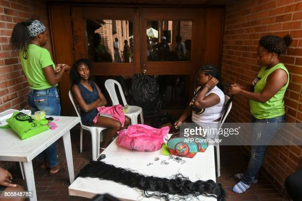 Two women get AfroColombian hairstyles during the 13th contest of Afro hairdressers Tejiendo Esperanzas in Cali Valle del Cauca department Colombia...
