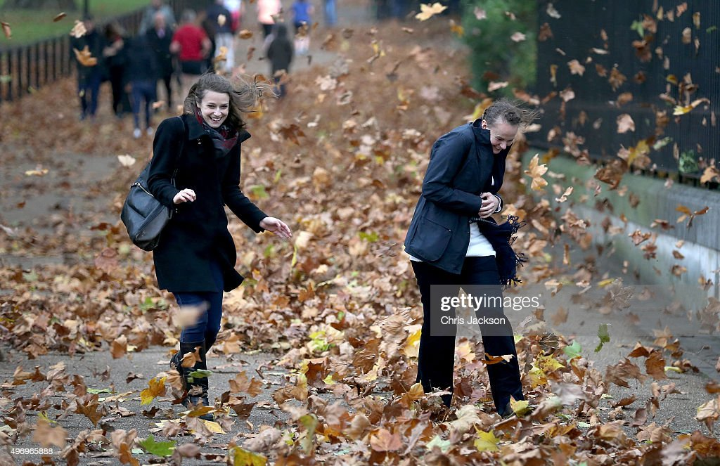 Two women get caught in gusts of wind during a rain storm in Green Park on November 13, 2015 in London, England.
