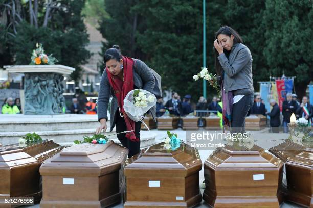 Two women give tribute by placing flowers on the coffins during the funeral of the 28 migrant women who died in a shipwreck as they sought to reach...