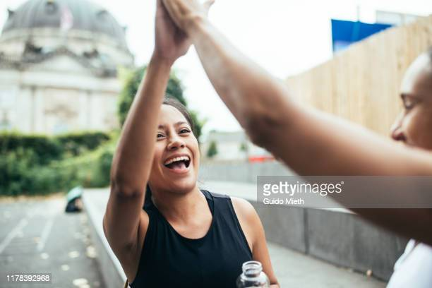 two women giving high five after workout challenge. - achievement stock pictures, royalty-free photos & images
