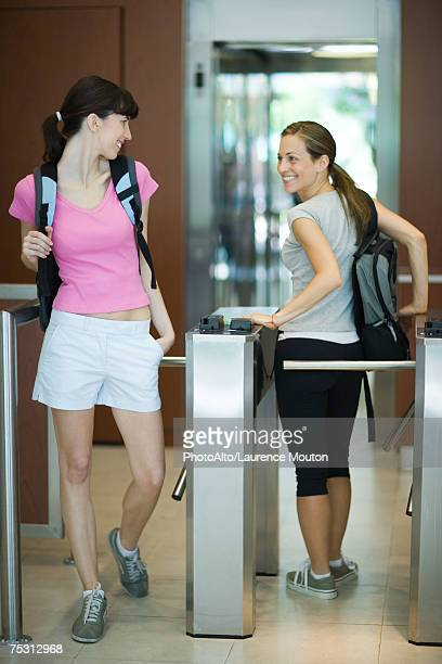 two women going through turnstile at health club, looking over shoulders at each other - 通過する ストックフォトと画像