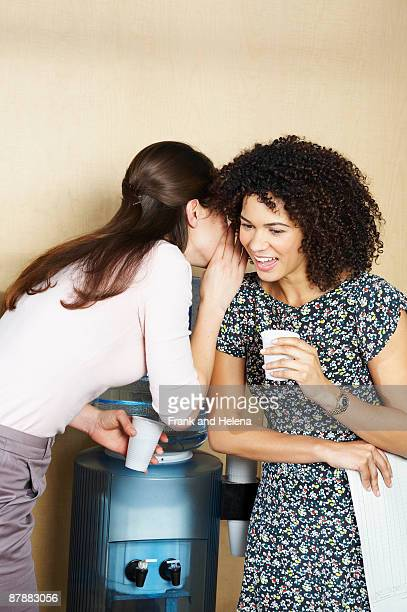 Two women gossiping by water cooler