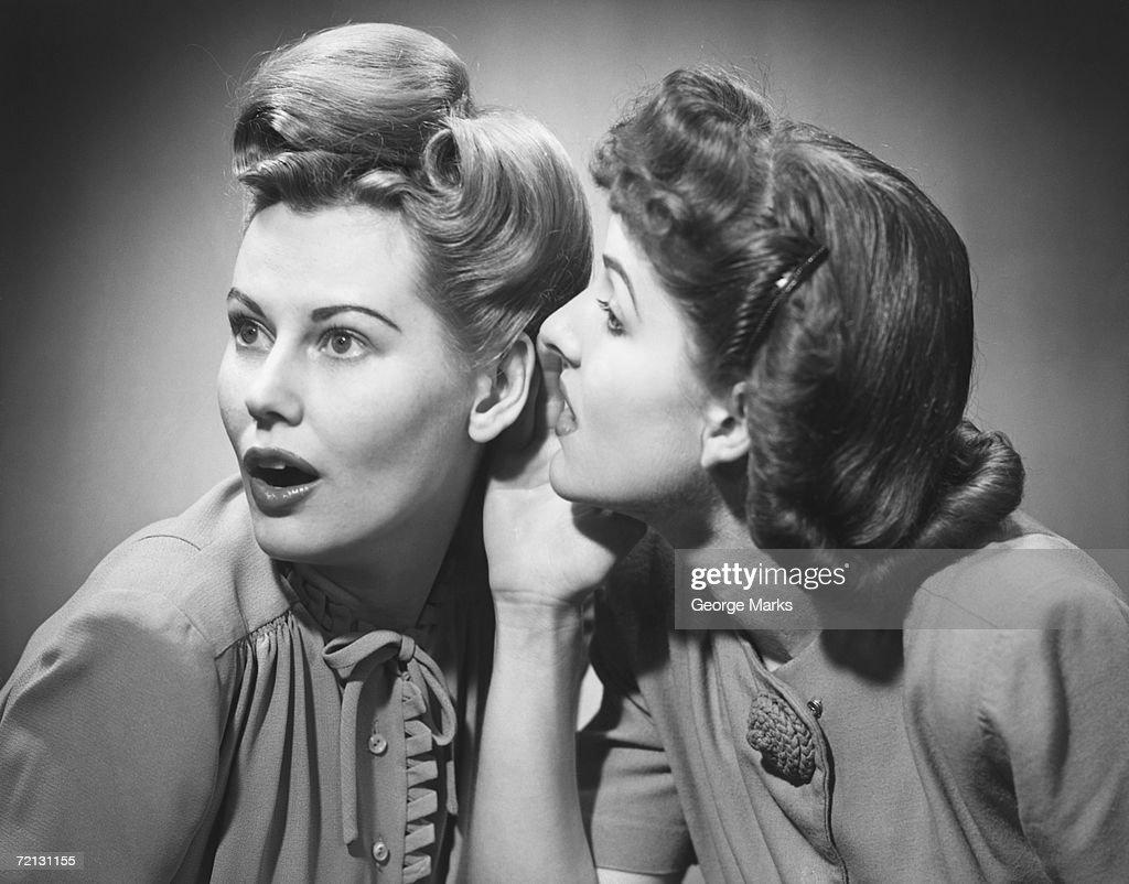 Two women gossiping in studio (B&W) : Stock Photo
