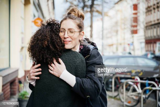 two women greeting one another in the street - black and white photos et images de collection