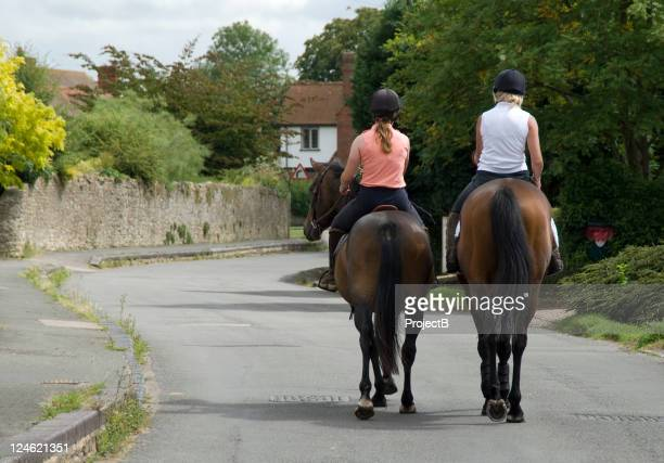 two women hacking out through a village - recreational horseback riding stock pictures, royalty-free photos & images