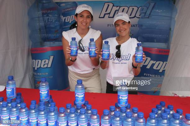 Two women handing out free Propel bottled fitness water at the Sport and Fitness Festival