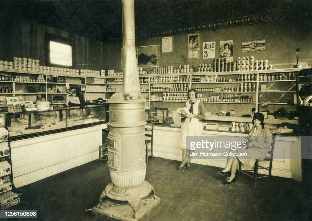 Two women hang out in a well-stocked grocery store, which has potbelly stove in the center of the floor, circa 1928.