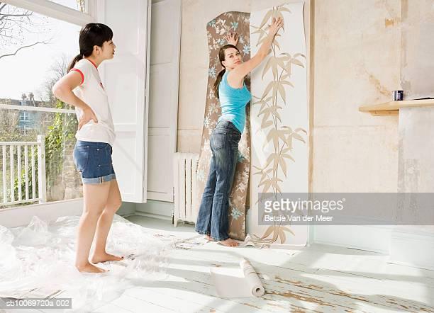 Two women hanging wall paper