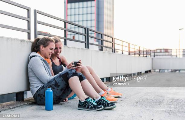 two women having a break from exercising sharing smartphone - net sports equipment stock pictures, royalty-free photos & images