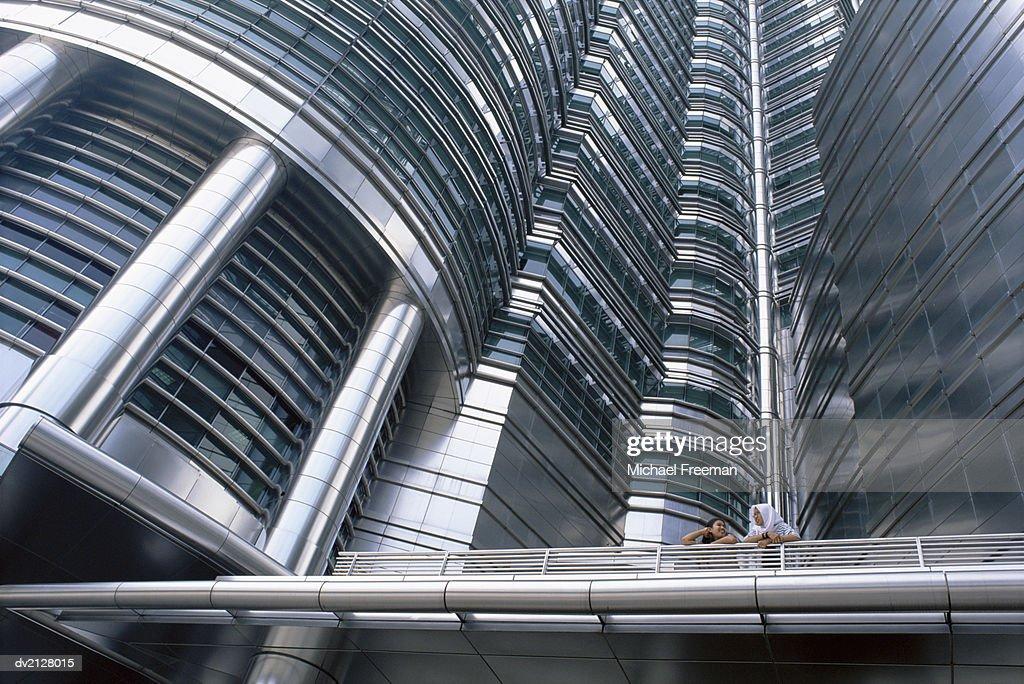 Two Women Having a Discussion at the Petronas Towers, Kuala Lumpur, Malaysia : Stock Photo
