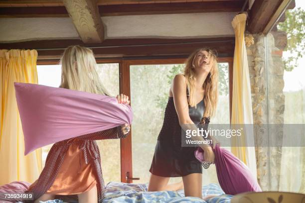 Two women having a pillow fight in bed