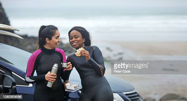 two women having food by car after surfing - weekend activities stock pictures, royalty-free photos & images