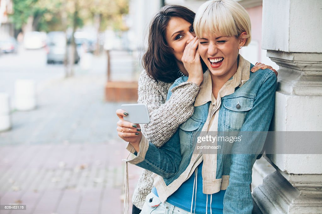 Two women having fun on street : Stock Photo