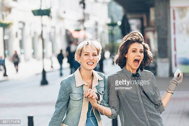 two women having fun on street - bisexuality stock photos and pictures