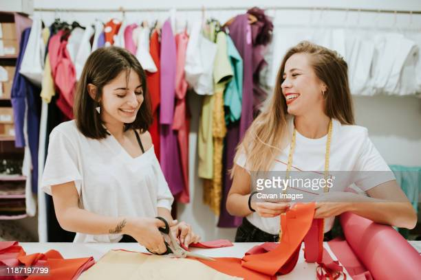 two women having fun together at work. fashion designers - fashion designer stock pictures, royalty-free photos & images